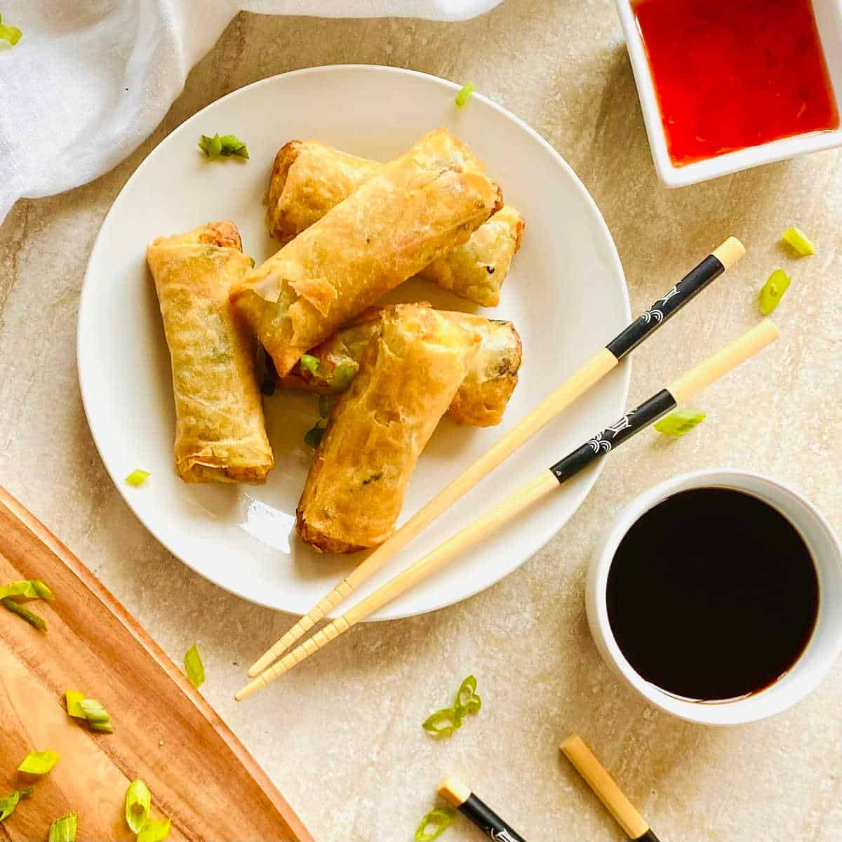 air fryer frozen spring rolls on a plate with chopsticks and soy sauce and thai chili sauce