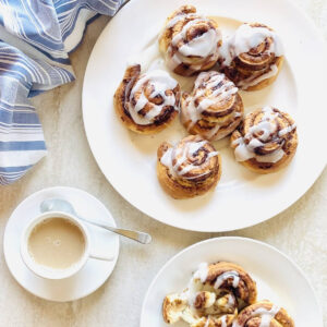 pillsbury air fryer cinnamon rolls on a plate next to coffee and a napkin