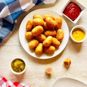 air fryer mini corn dogs on a plate next to ketchup and mustard