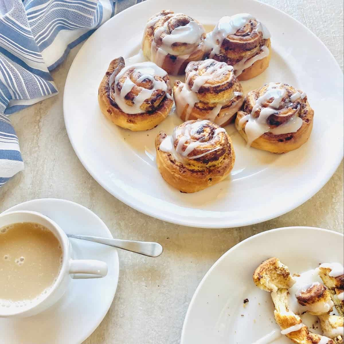 air fryer cinnamon rolls on a plate next to coffee and a napkin