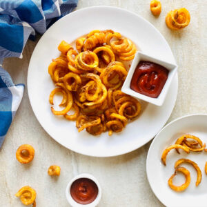curly fries air fryer on a plate next to ketchup