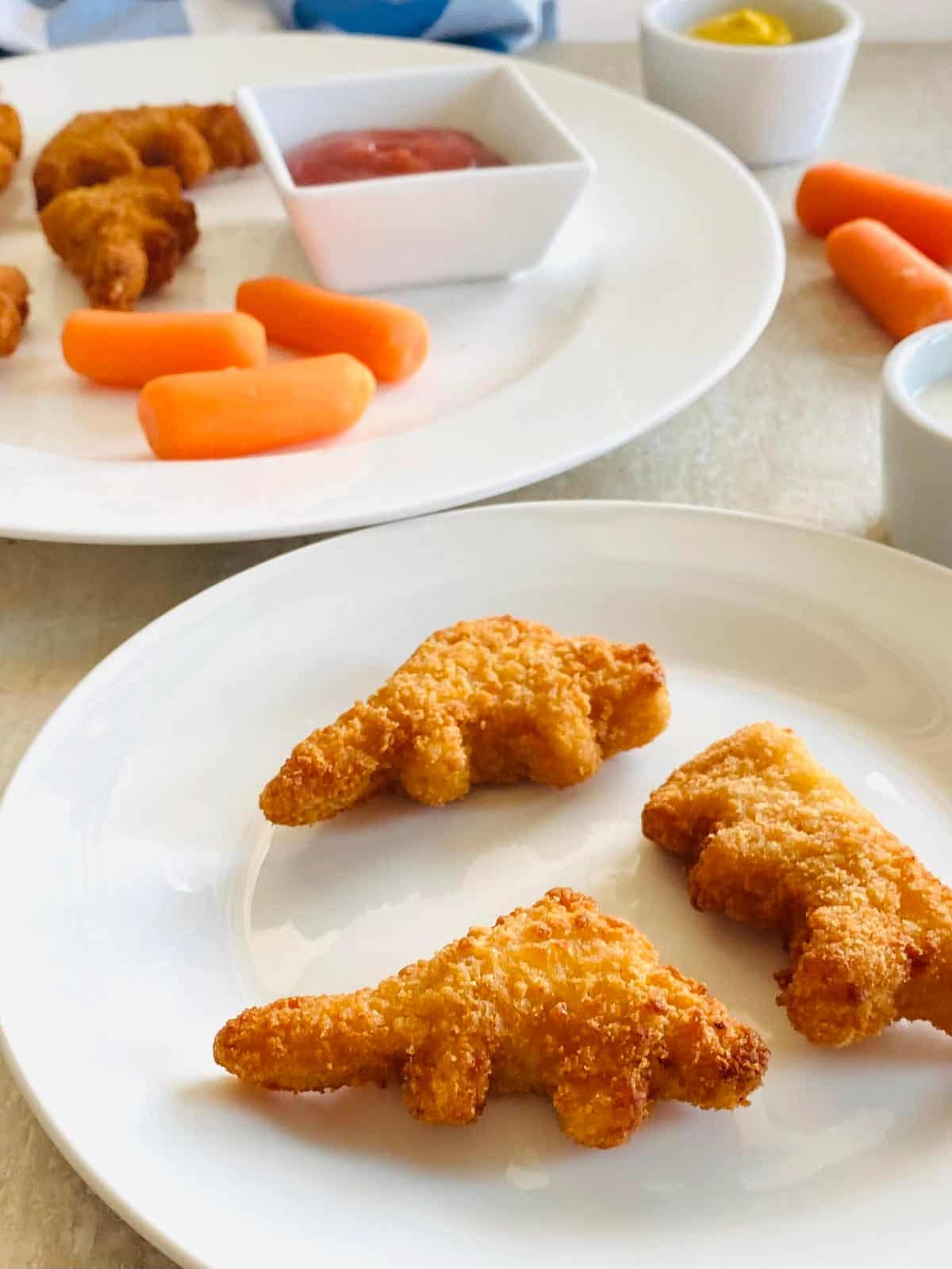 air fryer dino bites on a plate with carrots and dipping sauce
