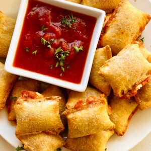 totinos air fryer frozen pizza rolls cooked on plate with marinara